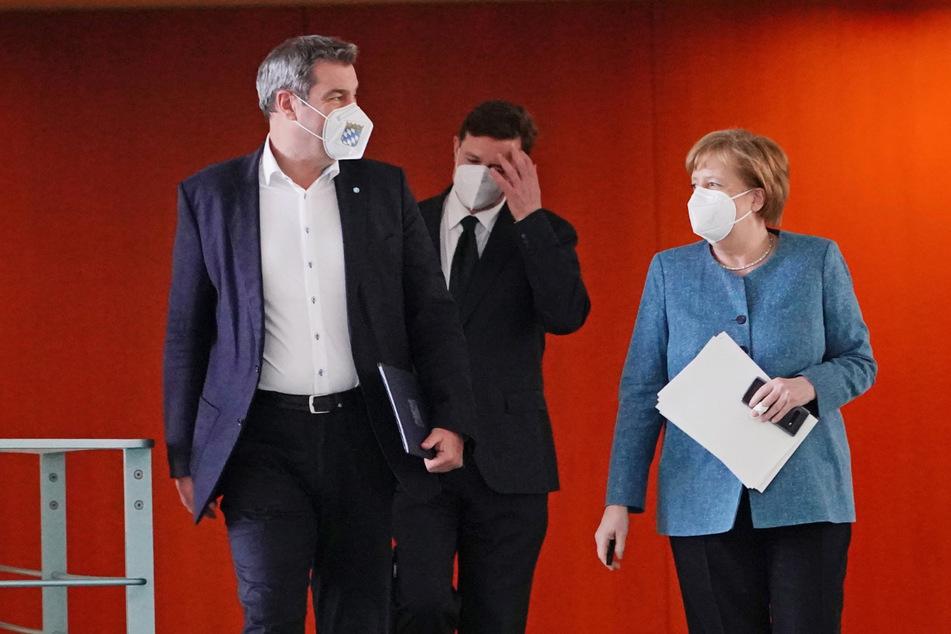 Bundeskanzlerin Angela Merkel (CDU) kommt neben Markus Söder (CSU, l), Ministerpräsident von Bayern und CSU-Vorsitzender, Zu der Pressekonferenz nach dem Impfgipfel im Kanzleramt.