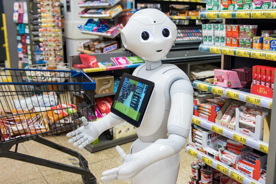 """Der humanoide Roboter mit dem Namen """"Pepper"""" steht in einem Supermarkt vor den Kassen."""