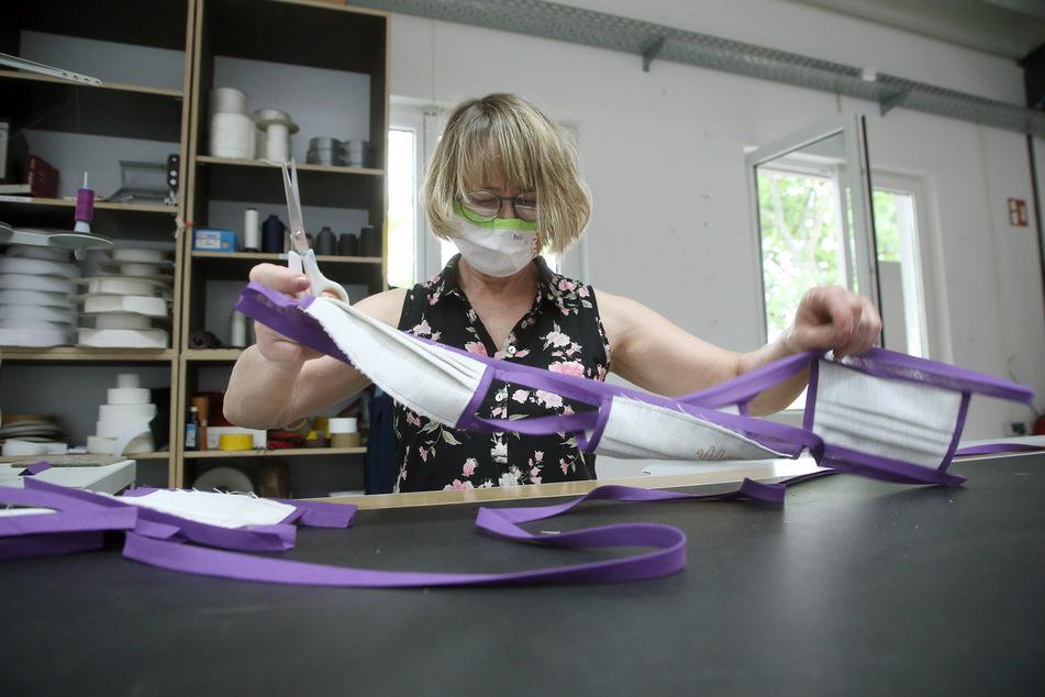 Eine Mitarbeiterin näht Bänder an Schutzmasken. (Symbolbild)