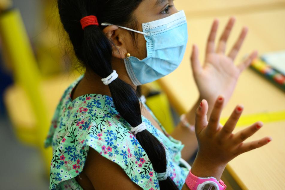 Das Foto zeigt eine Schülerin mit Mund-Nase-Maske in einem Frankfurter Klassenzimmer.