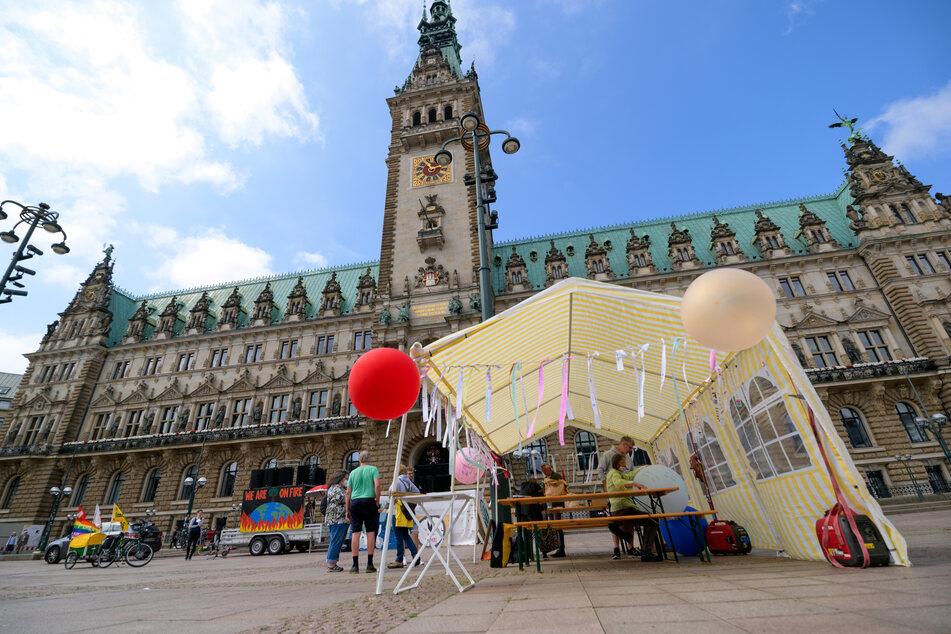 Mit bunten Bändern aus Stoff haben mehrere Menschen vor dem Hamburger Rathaus gegen die aktuelle Klimapolitik protestiert und gleichzeitig ihre Wünsche an die Regierenden formuliert.