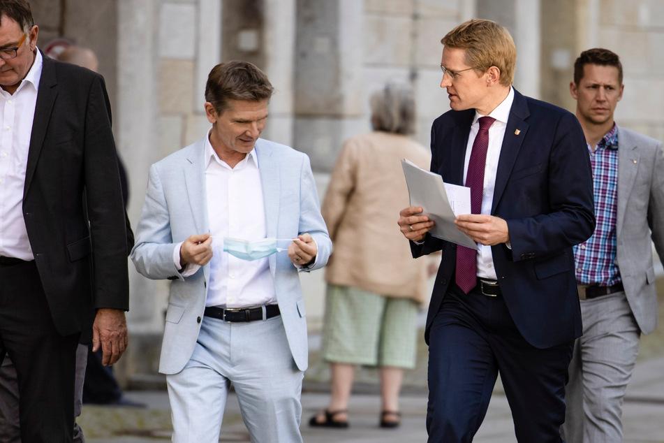 Schleswig-Holsteins Gesundheitsminister Heiner Garg (FDP, 2.v.l) und Daniel Günther (47, CDU, 3.v.l), Ministerpräsident von Schleswig-Holstein, sind auf dem Weg zu einer Pressekonferenz.