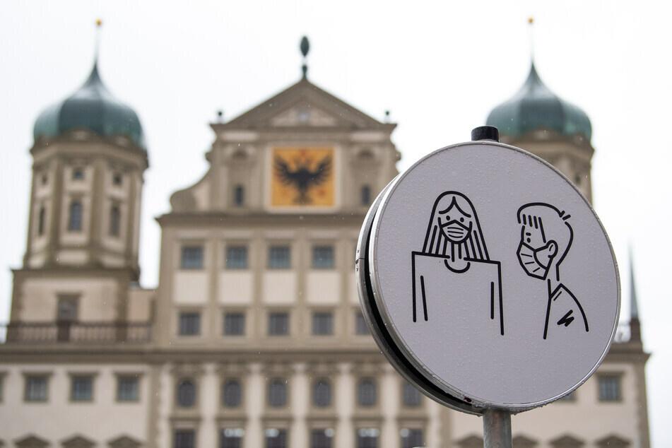 Eine Darstellung der Maskenpflicht ist auf einem Hinweisschild vor dem Rathaus in Augsburg zu sehen.(Archiv)