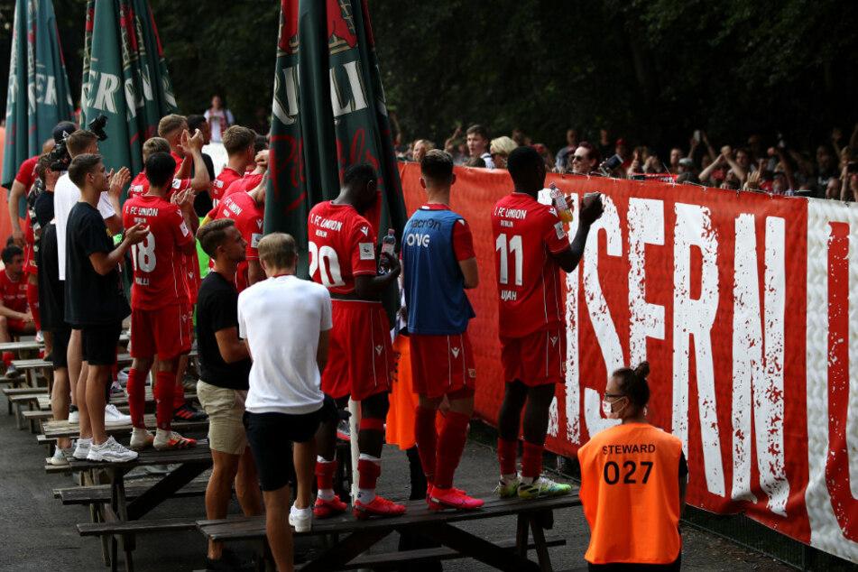 Die Spieler von Union Berlin feiern nach dem Spiel mit den Fans vor Ort.
