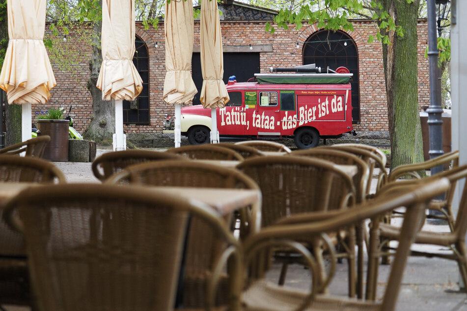 """Leere Tische und Stühle stehen im Biergarten der Braumanufaktur im Potsdamer Forsthaus Templin unter einem Zeltdach vor zusammengeklappten Sonnenschirmen und einem Feuerwehrauto mit der Aufschrift """"Tatüü, tataa — das Bier ist da""""."""