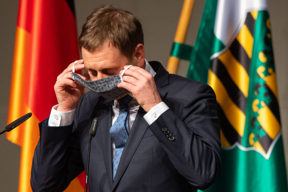 Michael Kretschmer (CDU), Ministerpräsident von Sachsen, zieht nach seiner Rede in der Sondersitzung des Sächsischen Landtages im ICC (Internationales Congress Center) seinen Mundschutz an.