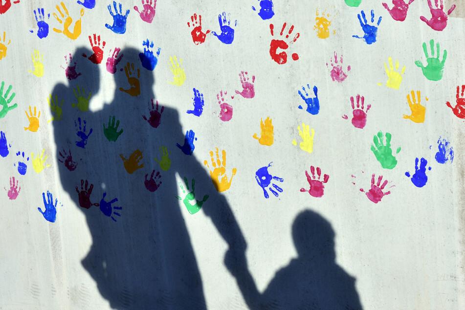 Ein Mann mit einem Kind auf dem Arm und einem an der Hand wirft einen Schatten auf eine mit bunten Handabdrücken bemalte Wand einer Kindertagesstätte.