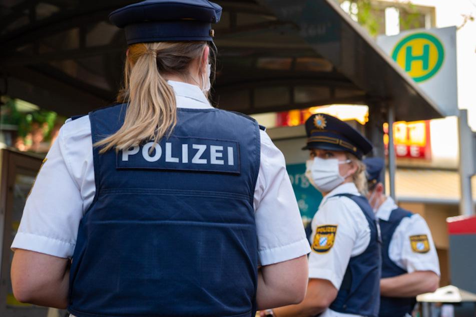 Drei Polizisten stehen an einer Haltestelle zur Maskenkontrolle.