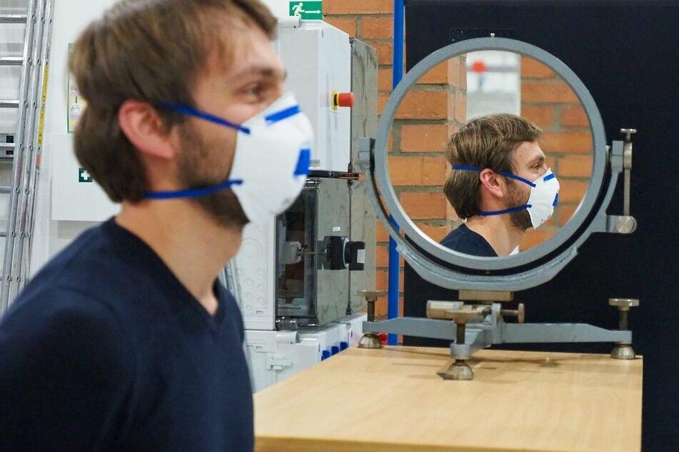TU-Freiberg-Mitarbeiter Emanuel Thom testet die Wirksamkeit einer Maske vor einem Schlierenspiegel, durch den Aerosole sichtbar gemacht werden.