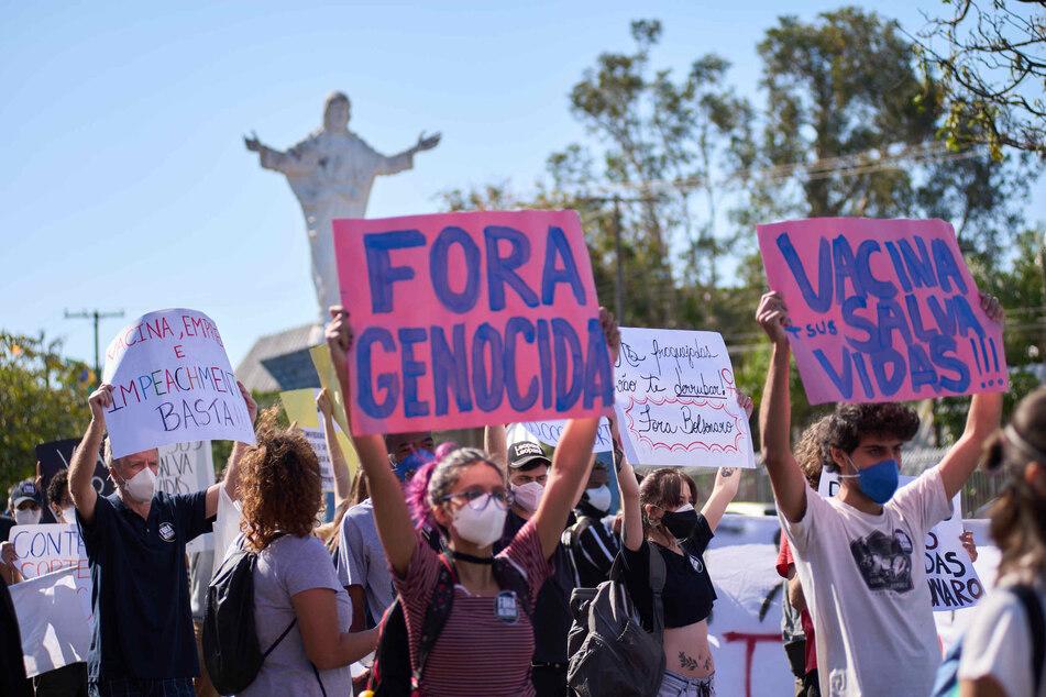 Demonstranten halten bei einem Protest Plakate auf denen Impfungen und die Absetzung von Präsident Bolsonaro gefordert wird.