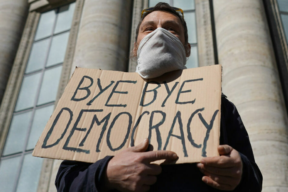 """Ein Transparente mit der Aufschrift """"Bye bye Democracy"""" wird bei einer Demonstration unter dem Motto """"Grundrechte verteidigen - Sage NEIN zur Diktatur!"""" auf dem Rosa-Luxemburg-Platz in die Höhe gehalten. (Symbolbild)"""
