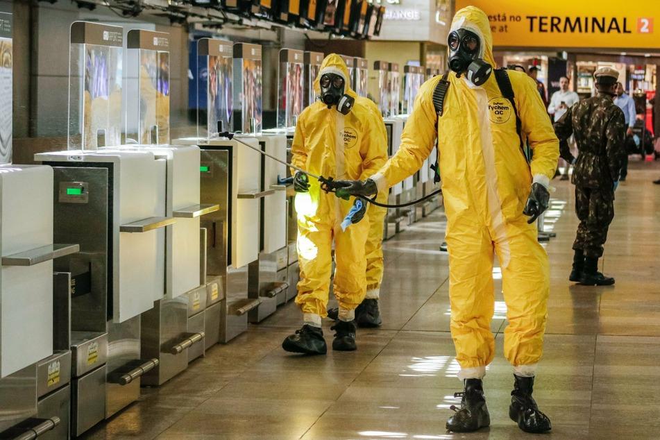 Mitglieder der Armee in Schutzanzügen führen einen Desinfektionseinsatz am internationalen Flughafen von Sao Paulo durch.