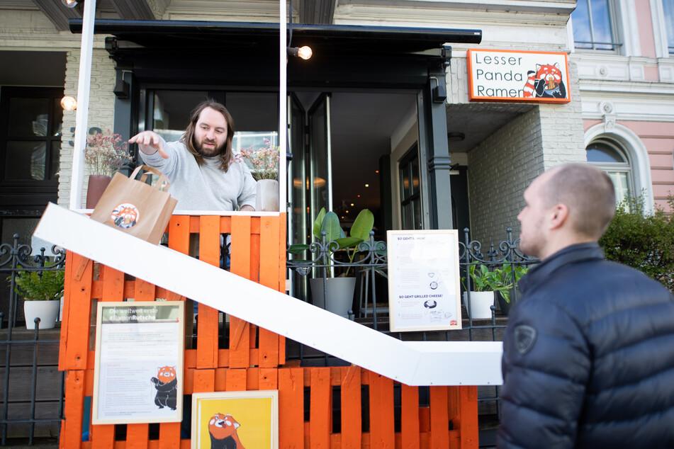 """Florian Ridder, Inhaber des Ramen-Restaurants, demonstriert die neue """"Ramen-Rutsche""""."""