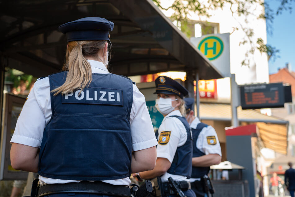 Drei Polizisten stehen an einer Tram-Haltestelle.