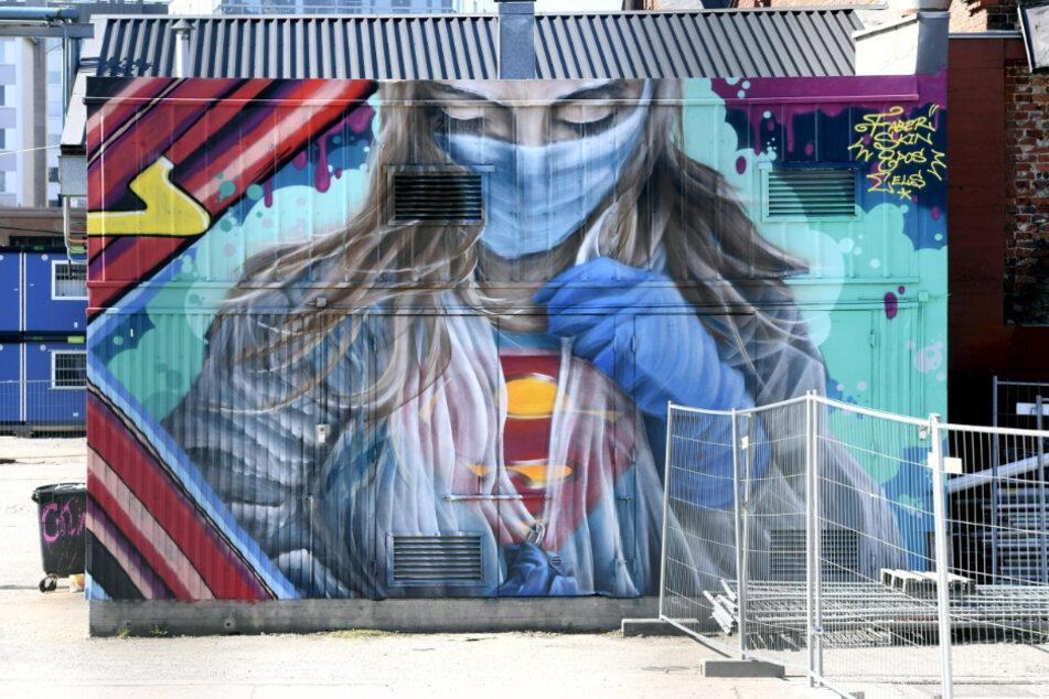 Finnland, Helsinki: Ein Wandbild zur Unterstützung und als Dank für medizinisches Personal im Kampf gegen die Corona-Pandemie, zeigt eine Ärztin mit Mundschutz im Superwoman-Kostüm.