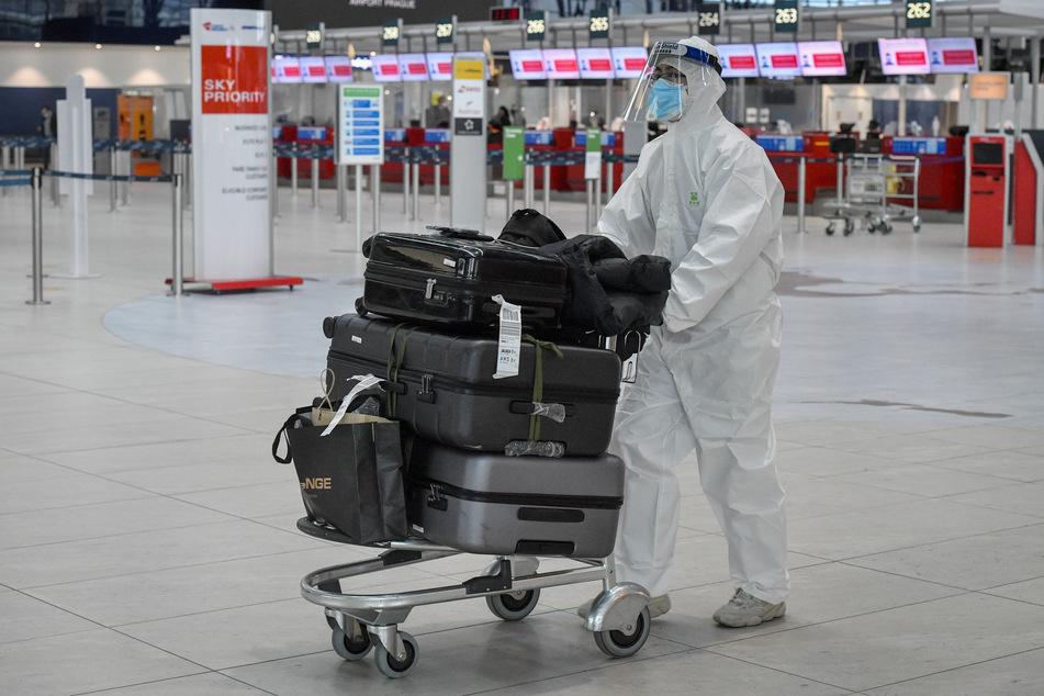 Tschechien, Prag: Ein Passagier, der zum Schutz vor dem Coronavirus einen Schutzanzug, Mund-Nasen-Schutz und Gesichtsvisier trägt, schiebt einen Gepäckwagen durch die Abflughalle des Flughafens Prag.