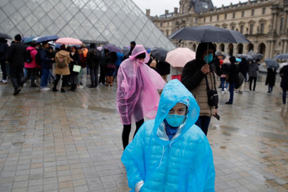 Touristen vor dem Pariser Louvre tragen Mundschutzmasken.