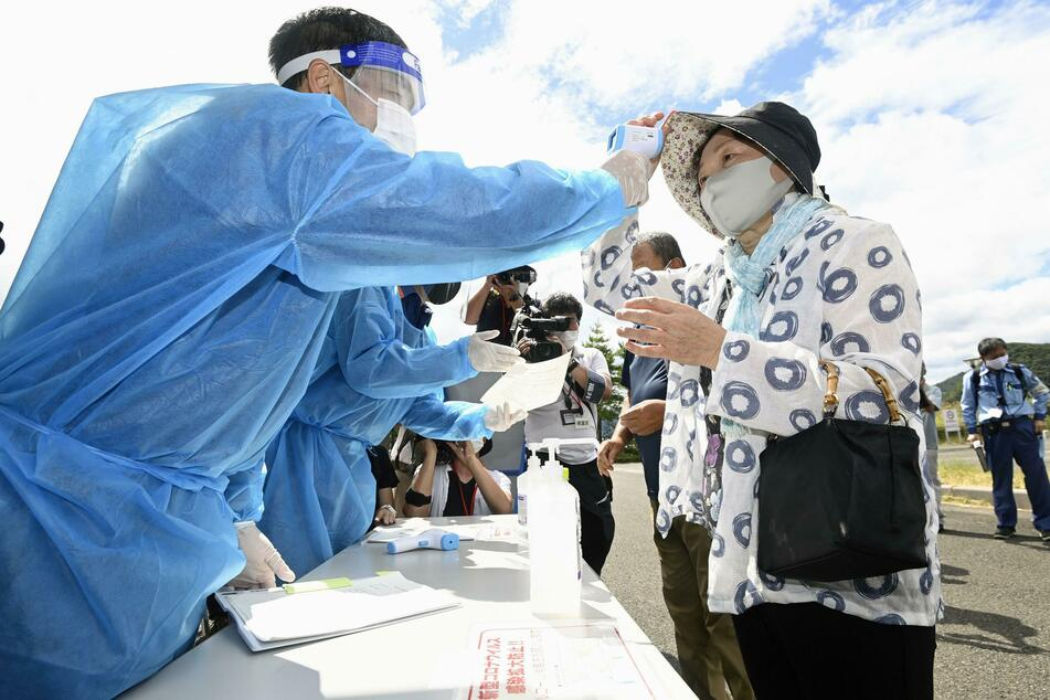 Die Teilnehmer einer Notfall-Evakuierungsübung werden auf ihre Temperatur überprüft.