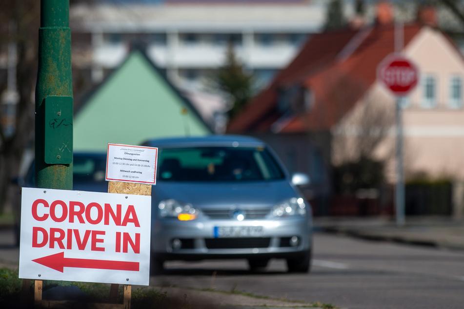 """""""Corona Drive-in"""" ist auf einem Schild an einer Zufahrt zu einem Parkplatz zu lesen. In Schönebeck besteht die Möglichkeit mit dem eigenen Fahrzeug direkt vor einen Wohnwagen zu fahren."""