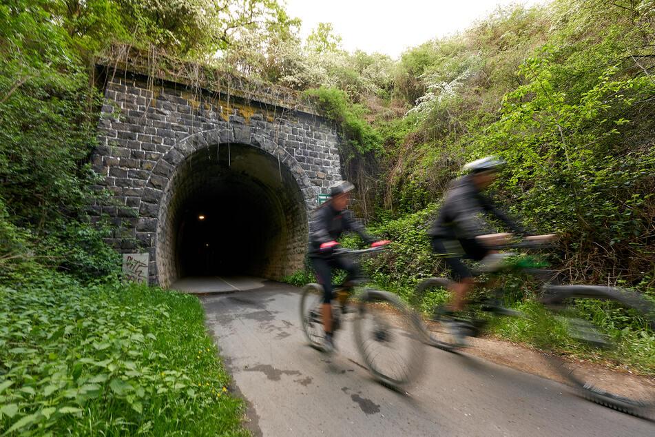 Zwei Radfahrer kommen auf dem Maifeld-Radweg, der auf der Trasse einer stillgelegten Bahnstrecke verläuft, aus einem Tunnel (Symbolbild).
