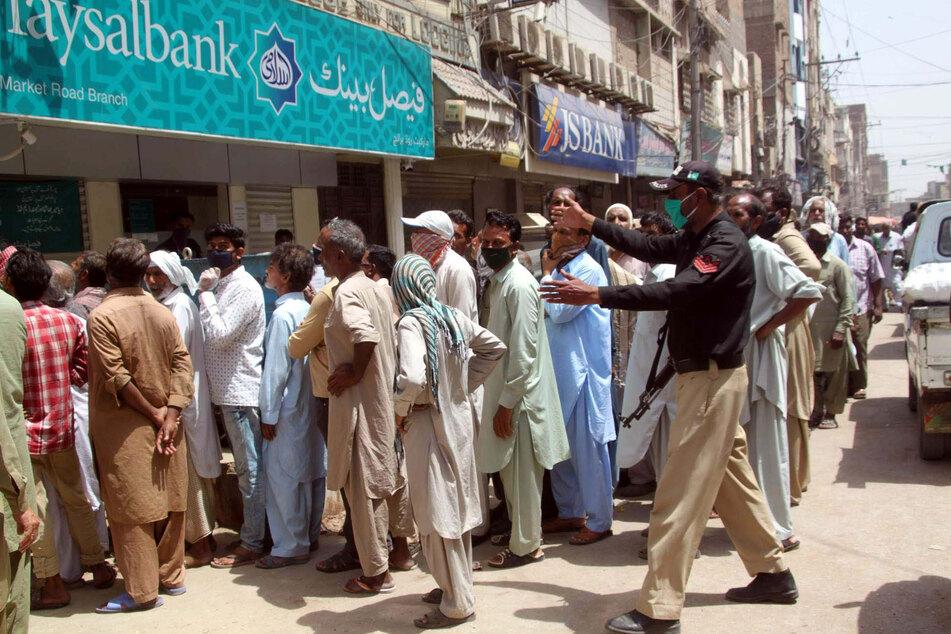 Menschen versammeln sich ohne Sicherheitsabstand vor einer Bank in Pakistan.