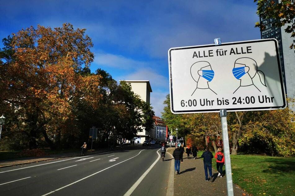 Eines der Schilder weist in der Universitätsstraße auf das Tragen einer Mund-Nasen-Bedeckung hin.