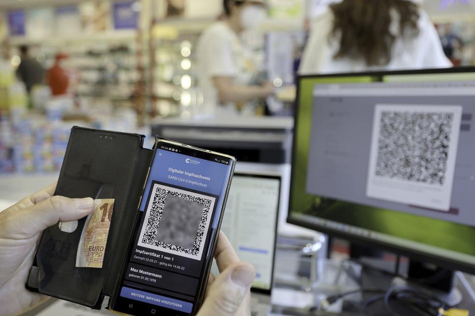 Der digitale Impfnachweis ist auf einem Smartphone in einer Apotheke zu sehen. Ein Teil der Apotheker startet mit dem Ausstellen des neuen digitalen Nachweises einer Corona-Impfung.