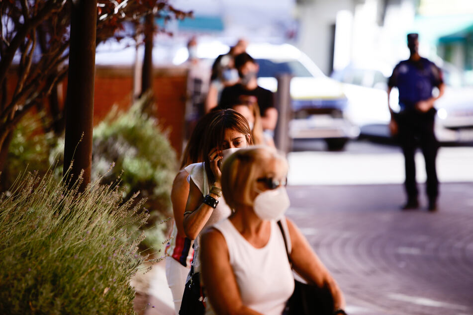 Menschen mit Mundschutz stehen vor einem Covid-19-Testzentrum in Madrid Schlange, um sich testen zu lassen.