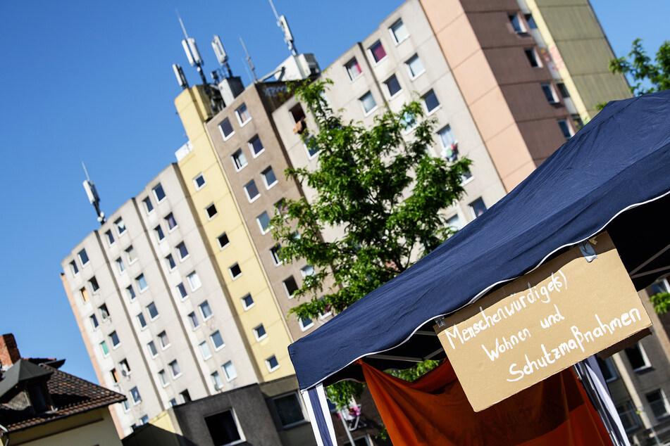 """""""Menschenwürdige(s) Wohnen und Schutzmaßnahmen"""" steht auf einem Plakat vor einem unter Quarantäne gestelltem Wohngebäude."""