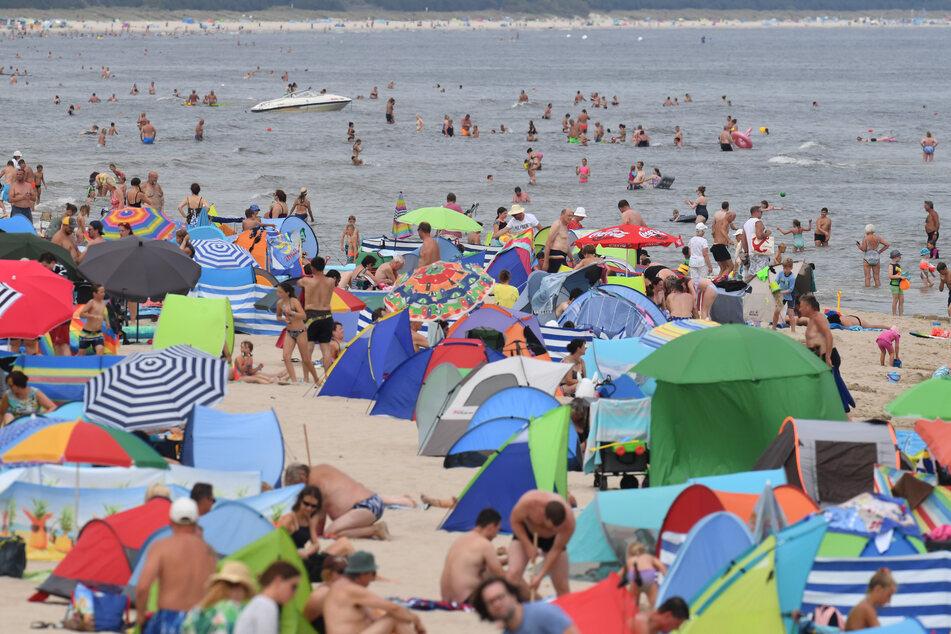 Am Ostseestrand vor der Seebrücke in Zinnowitz haben sich zahlreiche Badegäste bei warmen Lufttemperaturen am Strand niedergelassen oder genießen das Wasser.