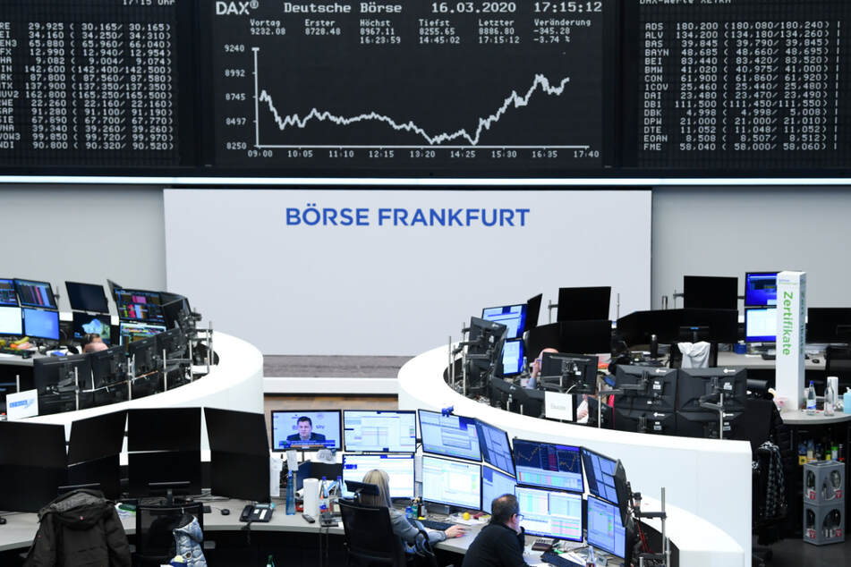 Aktienhändler arbeiten im Handelssaal der Frankfurter Wertpapierbörse vor der Anzeigetafel mit der Dax-Kurve.