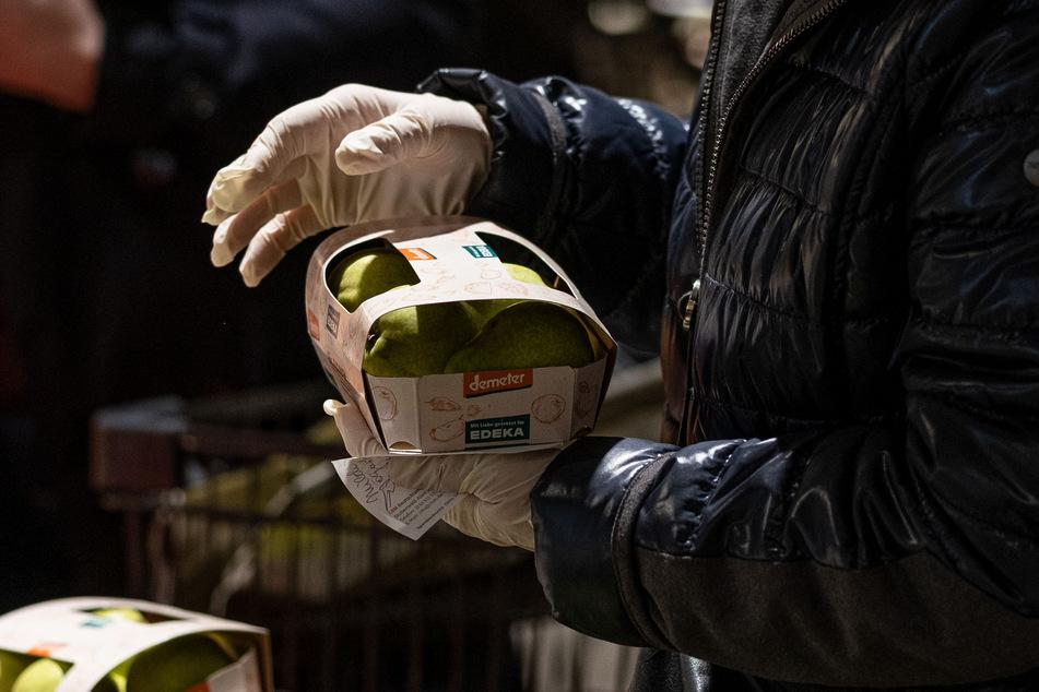 Mit Gummihandschuhen kauft eine Frau in einem EDEKA Markt ein.
