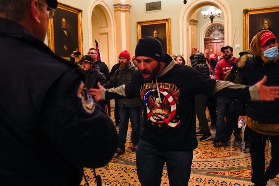 Demonstranten gestikulieren vor der US-Kapitol-Polizei auf dem Gang vor der Senatskammer im Kapitol.