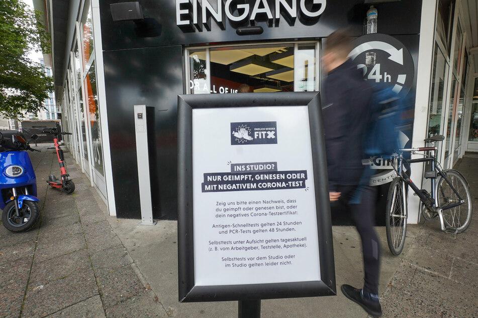 """Ein Schild, das darauf hinweist, dass eines der """"3Gs"""" (geimpft, genesen, getestet) erfüllt sein muss, steht vor einem Fitnessstudio am Alexanderplatz."""