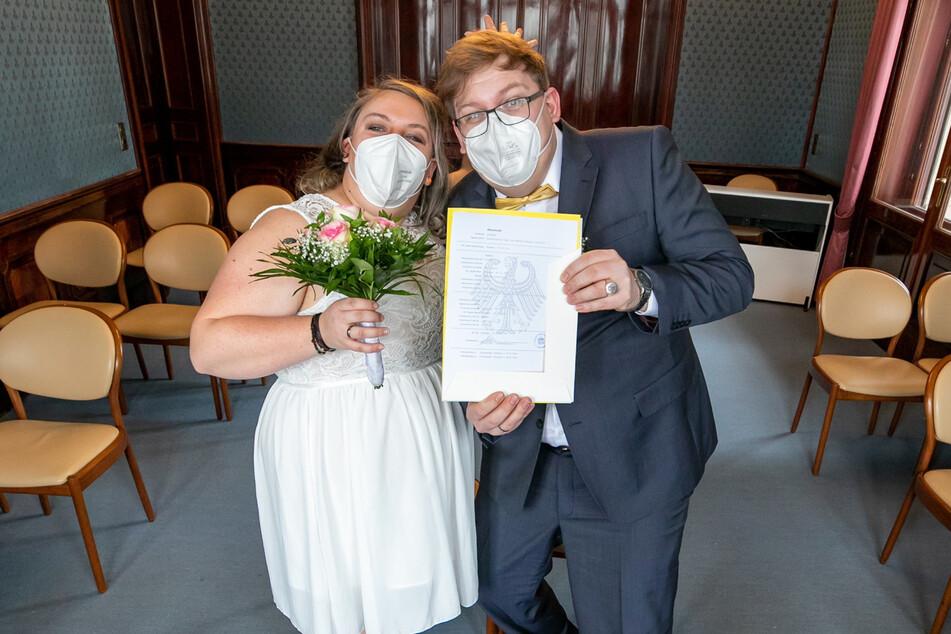 Stolz zeigt das Ehepaar die Heiratsurkunde.