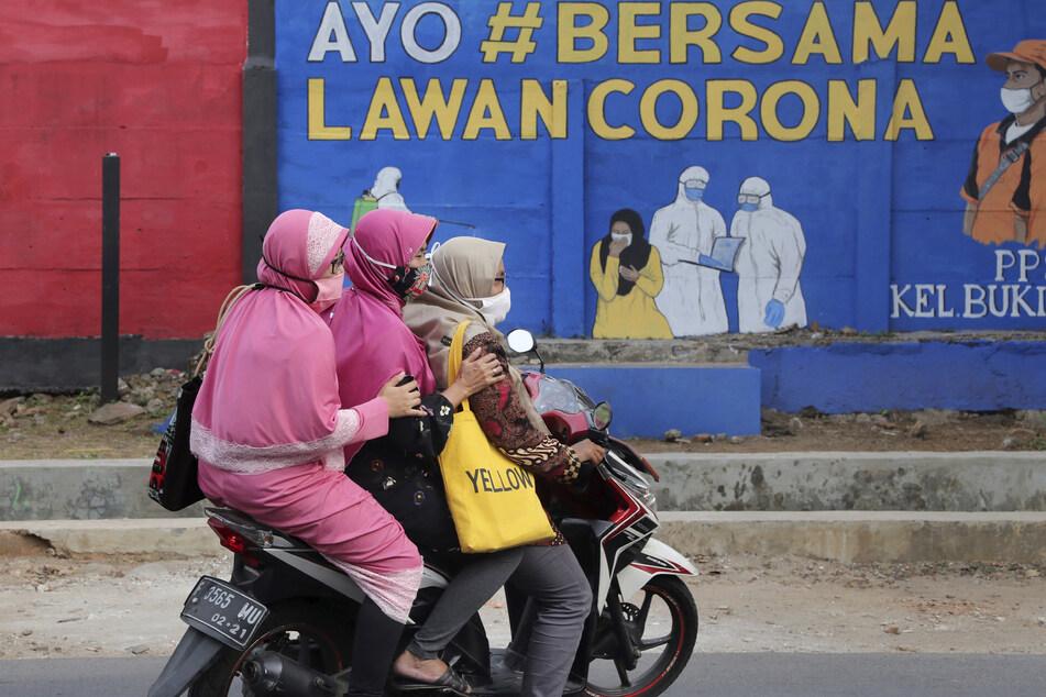 """Drei Frauen fahren auf einem Roller an einem, Wandgemälde vorbei auf dem zu lesen ist """"Zusammen bekämpfen wir das Virus""""."""
