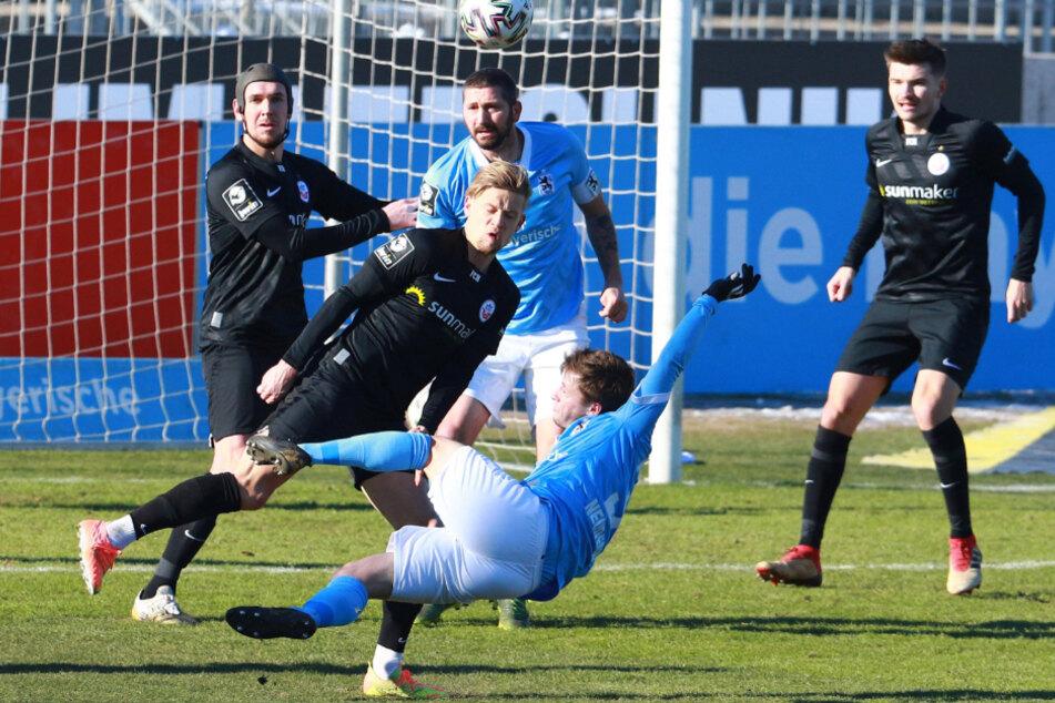Richard Neudecker (vorn) und Sascha Mölders (M, hinten) von den Löwen kämpfen gegen die Rostocker Damian Roßbach (l.) und Nico Neidhart um den Ball.