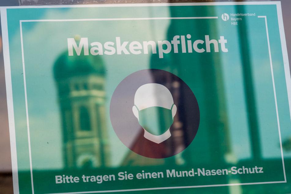 """Ein Schild mit der Aufschrift """"Maskenpflicht"""" hängt in der Tür zu einem Geschäft in der Münchner Innenstadt."""