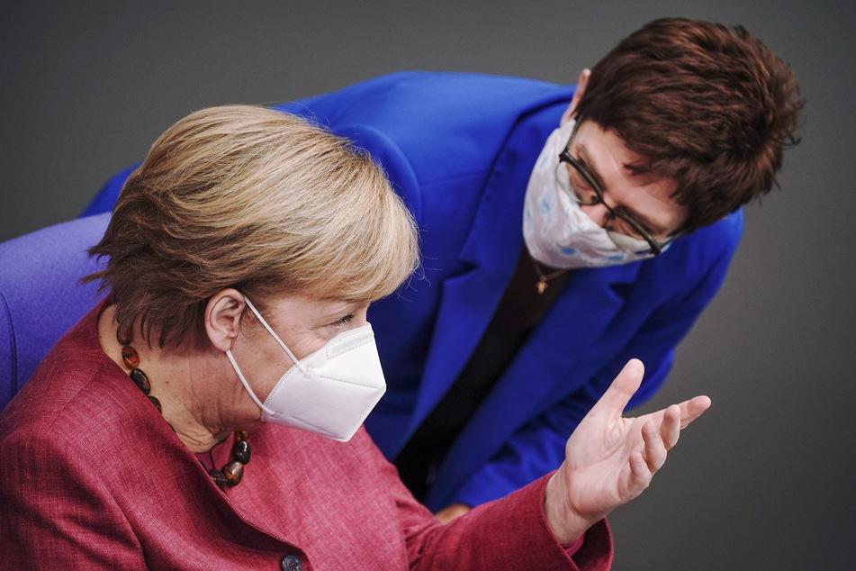Bundeskanzlerin Angela Merkel (l) und Annegret Kramp-Karrenbauer (beide CDU), Bundesministerin der Verteidigung und CDU-Bundesvorsitzende, unterhalten sich mit Mund-Nasenbedeckung in der Sitzung des Bundestags. Kramp-Karrenbauer widerspricht der Kritik ihres Parteikollegen Friedrich Merz.