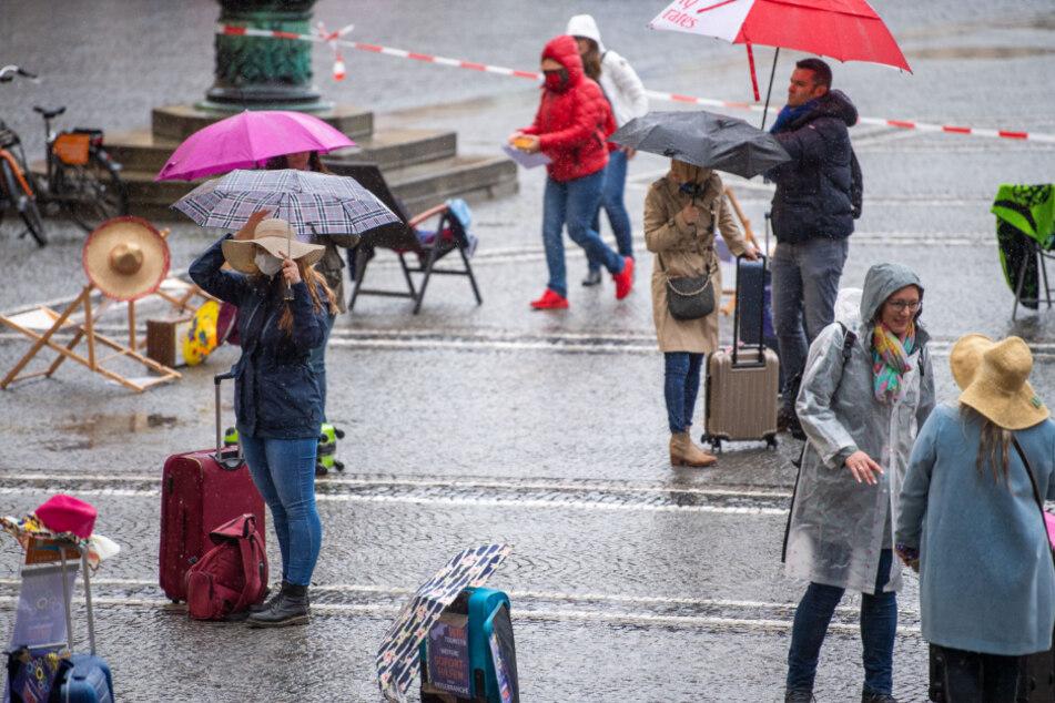Demonstranten mit Koffern stehen am Odeonsplatz im Regen. Reiseveranstalter haben bundesweit für einen Rettungsschirm gestreikt.