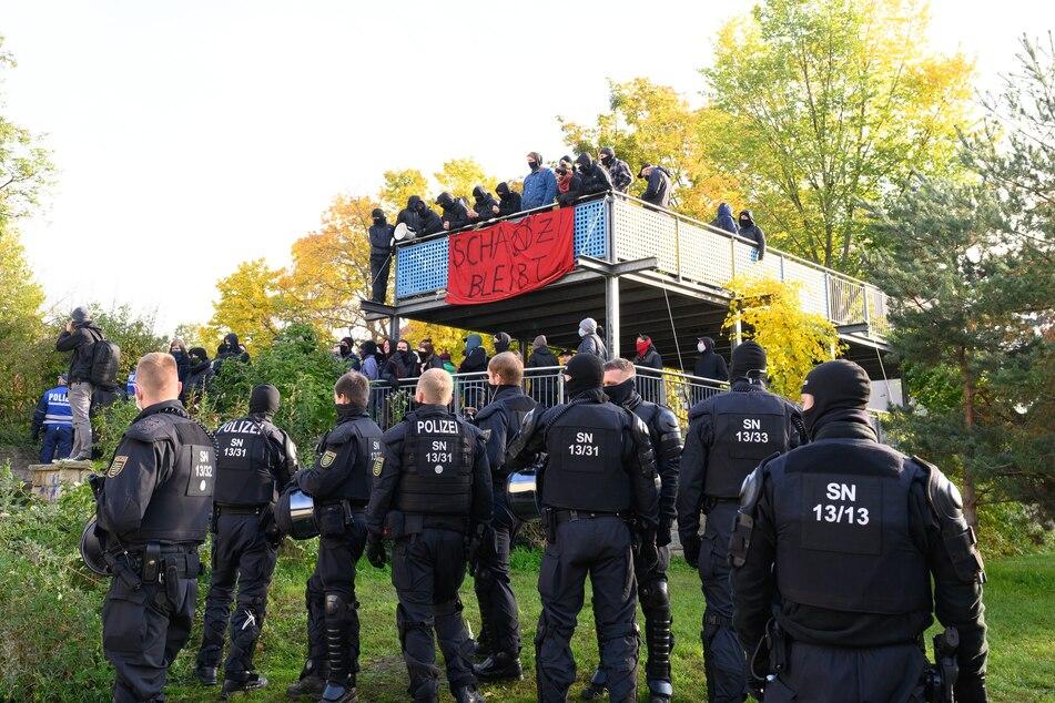 Polizisten und Aktivisten stehen während einer Durchsuchung eines besetzten Hauses im Pauli Park.
