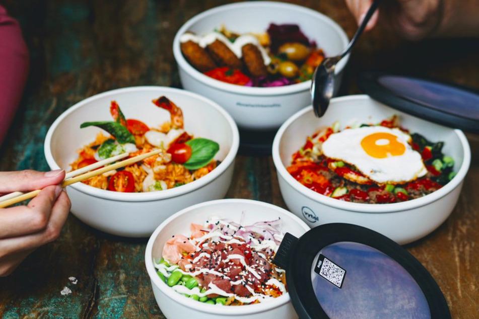 Mehrere Personen essen aus Mehrwegschalen des Kölner Start-ups Vytal.