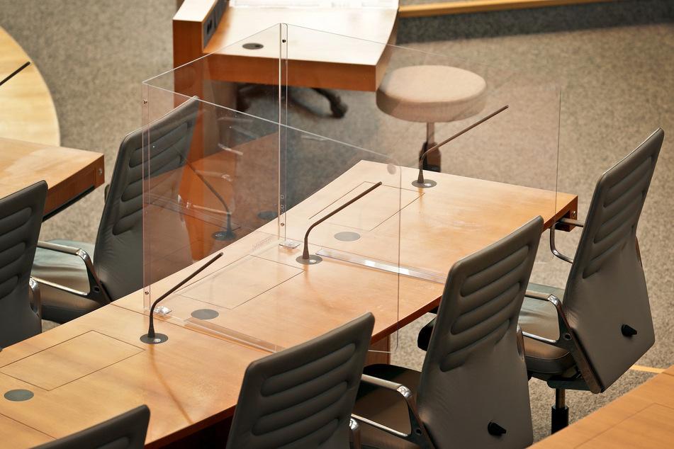 Der Prototyp einer Acrylglas-Kabine steht im Plenarsaal des nordrhein-westfälischen Landtages auf dem Tisch der Abgeordneten.