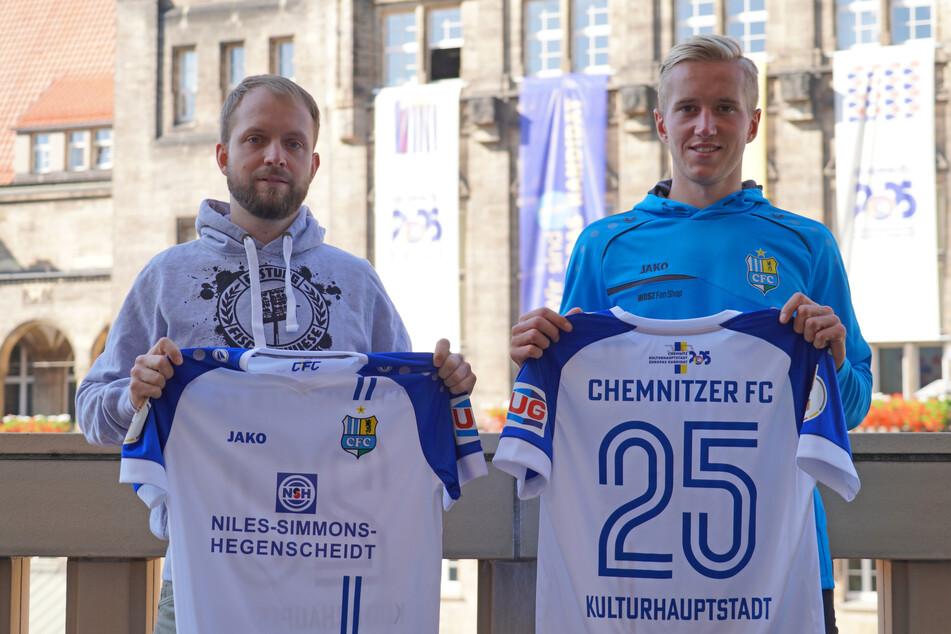 Niels Vogt (links, Vorstandsmitglied des Fanszene Chemnitz e.V.) und CFC-Stürmer Alexander Dartsch präsentieren das Stadttrikot.