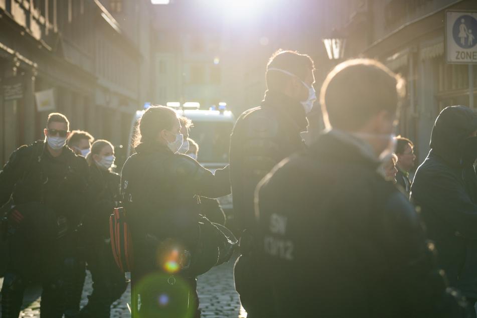 Polizisten stehen am Rand einer Demonstration von Gegnern der Corona-Maßnahmen auf dem Marktplatz von Pirna in einer Seitenstraße.