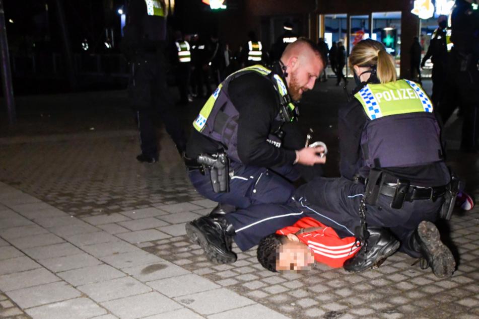 Polizisten nehmen einen jugendlichen Randalierer in Gewahrsam.