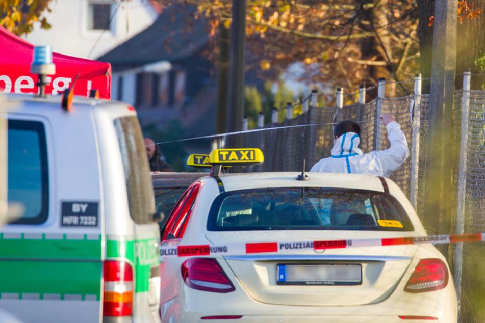 in Mitarbeiter der Spurensicherung arbeitet an einem Tatort auf einer Straße, in der zuvor zwei Menschen erschossen wurden.