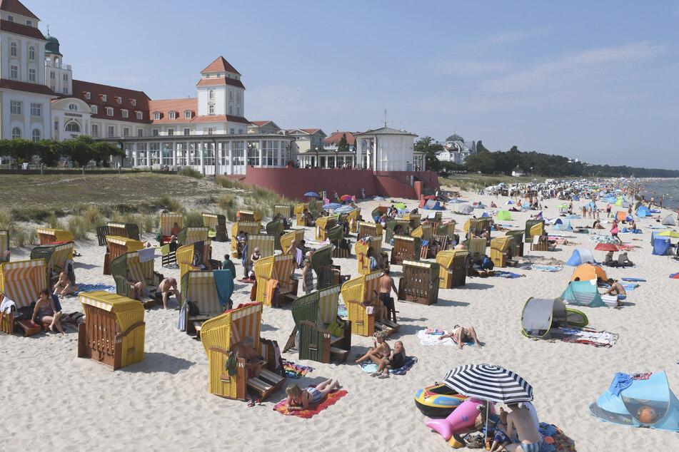 Mecklenburg-Vorpommern, Binz: Am Ostseestrand vor der Seebrücke haben sich Badegäste niedergelassen.