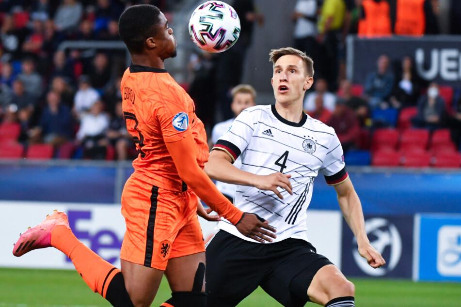 Deutschlands Nico Schlotterbeck (21, r.) und Myron Boadu (20) von den Niederlanden kämpfen im Halbfinale der U21-EM um den Ball.