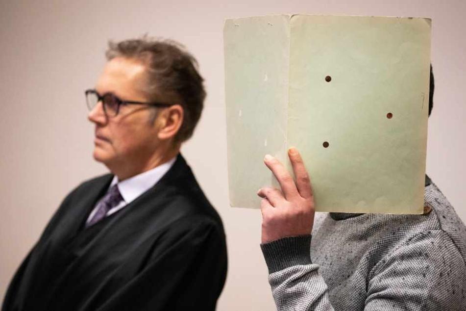 Der Angeklagte versteckt sich neben seinem Anwalt hinter einer Mappe.